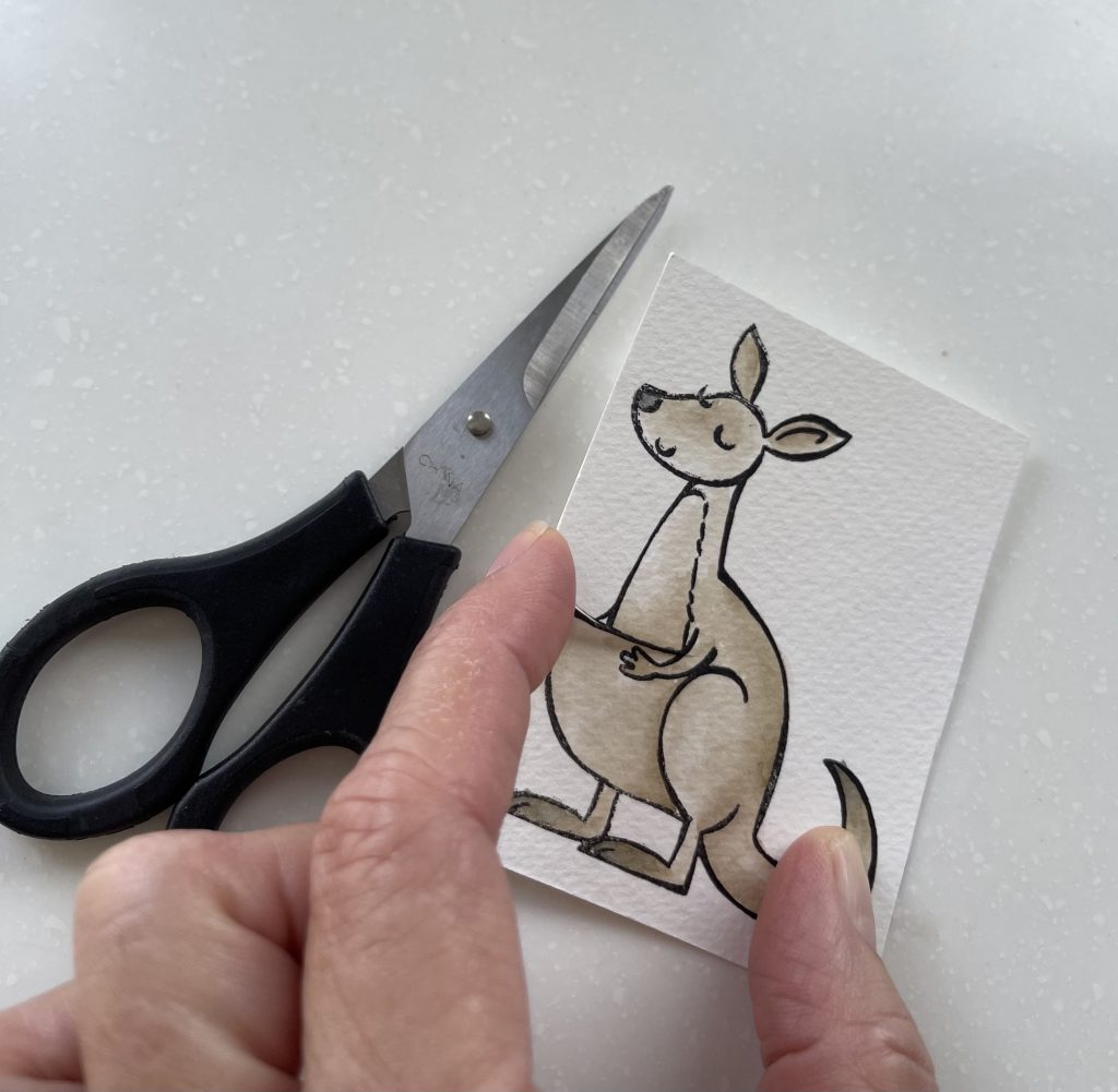 Cut a slit with scissors to fit the joey into the pouch